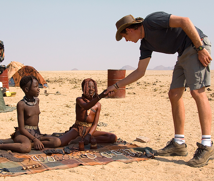 A traveller meets Himba girls - one has begun her passage to womanhood and is adorned with the ochre mixture that reddens her skin.