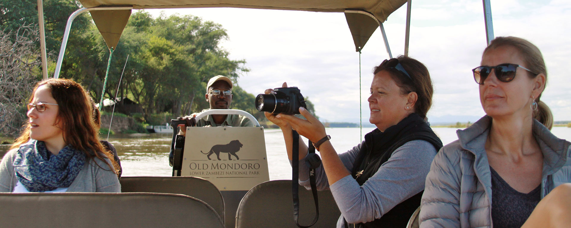 Go2Africans Liesel, Natasha and Rikke enjoying a river transfer from Old Mondoro to Chiawa – herds of elephants are frequently spotted drinking at the water's edge.