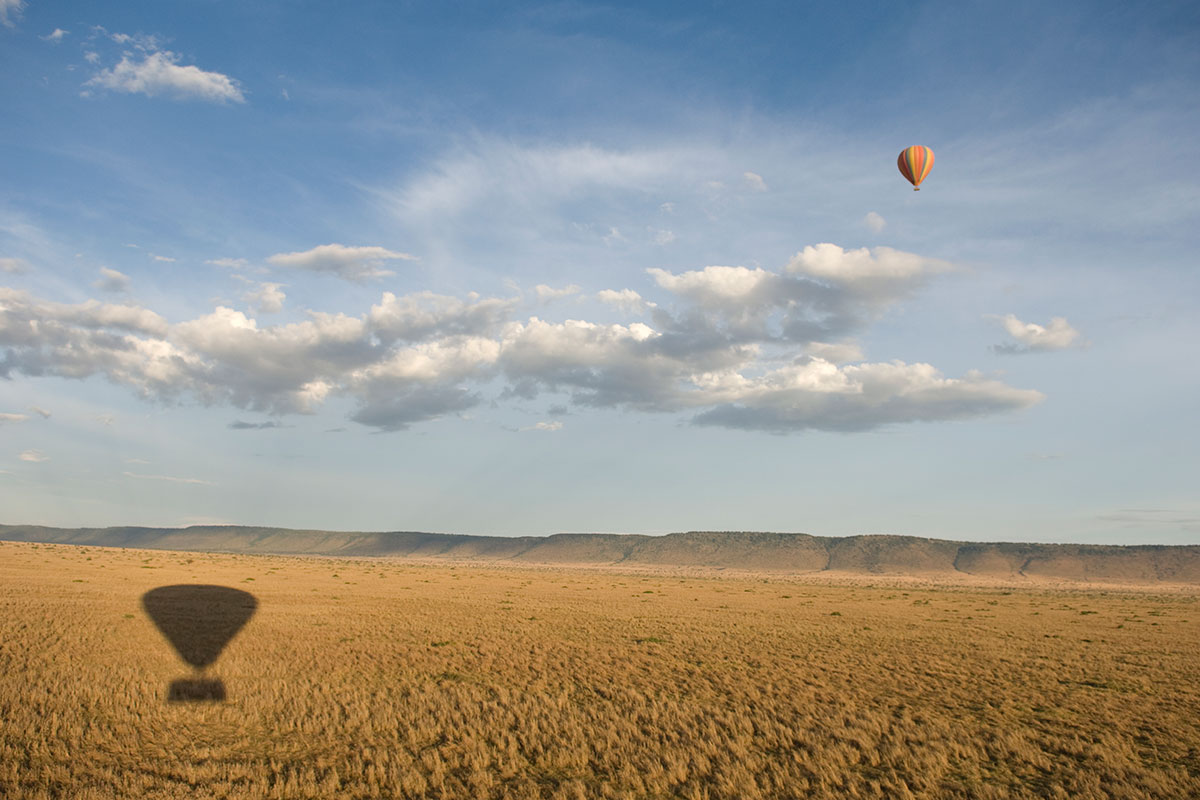 Safari on a hot air balloon casting a shadow on the Masai Mara, Kenya