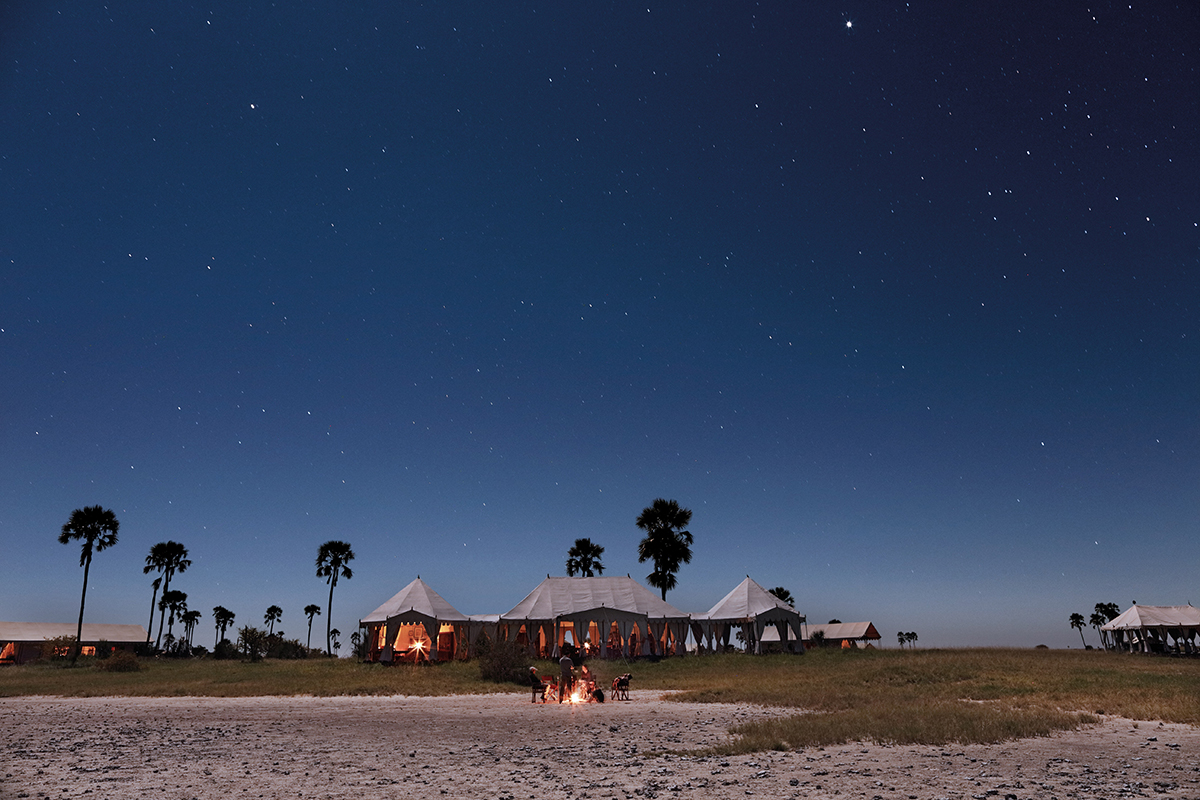 Group sit by fire outside San Camp under the Kalahari Desert night sky | Botswana Safari | Go2Africa