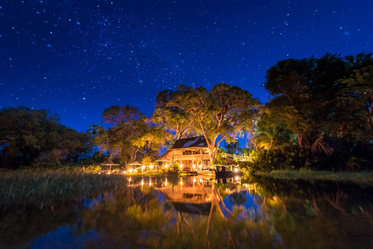 Night time exterior view of the intimate & luxurious Jacana Camp in the Okavango Delta