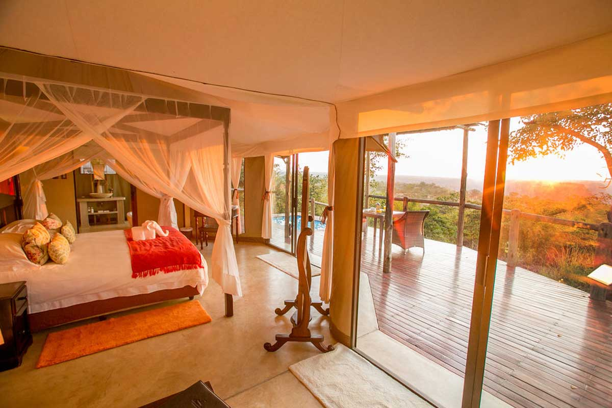The Elephant Camp suite interior with uninterrupted views of Victoria Falls National Park bushland.